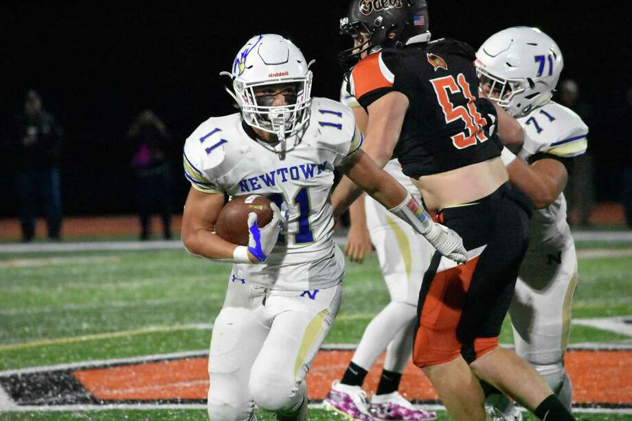 Newtown's Miles Ricks runs the ball against Shelton at Finn Stadium, Shelton on Friday. Photo: Pete Paguaga / Hearst Connecticut Media / Connecticut Post