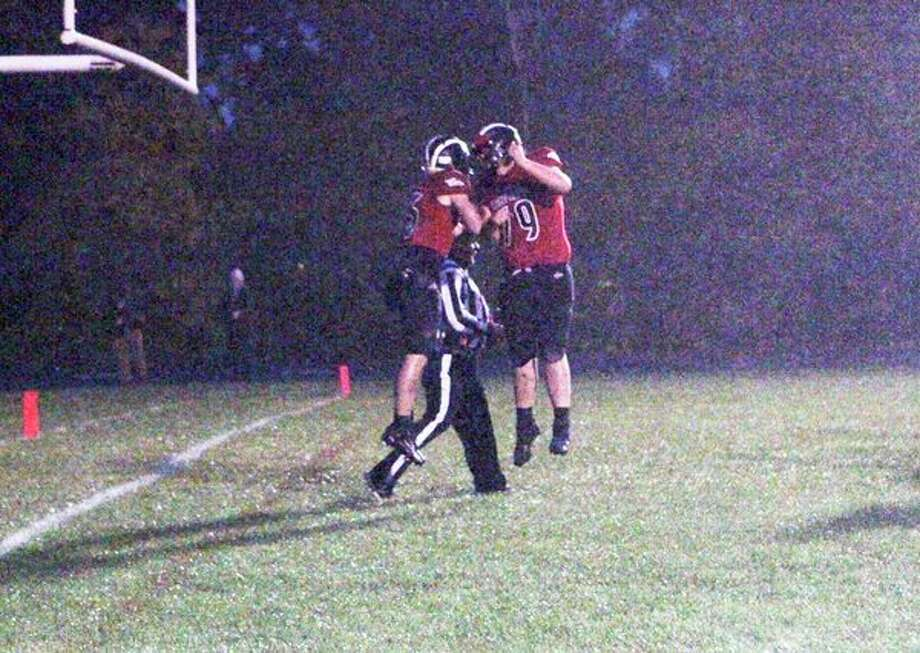 Reed City's Payton Hansen and Darrin Halladay celebrate with each other after Hansen scored his first touchdown of the night for the Coyotes during Friday's homecoming game against Central Montcalm. (Pioneer photo/Joe Judd)