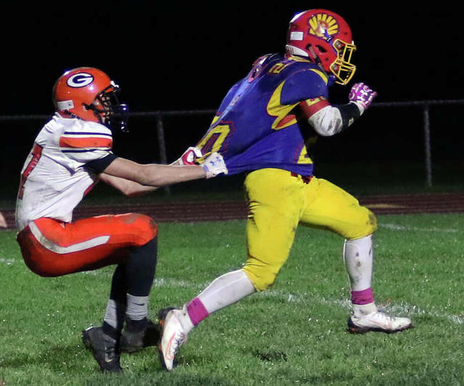 Gillespie's Joseph Baglin (left) holds onto the jersey of Roxana running back Michael Ilch before taking him down after a 25-yard run to the Miners' 7-yard line in the fourth quarter Friday night at Raich Field in Roxana. Ilch scored two plays later to seal the Shells' 30-16 victory. Photo: Greg Shashack | The Telegraph