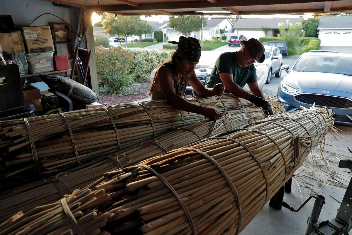 Antonio Moreno, an Ohlone Indian, works with his friend Alfonso Ramirez on the construction of a Tule reed water vessel at Ramirez's home in Fremont, Calif., on Friday, October 11, 2019. Moreno and Ramirez and other members of the tribe will paddle to Alcatraz Island on Indigenous Peoples' Day to commemorate the occupation of the island by local Indian tribes in 1969.
