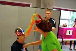 """Sheriff John O'Hagan (background), alias """"Johnny O"""" made an appearance at the Manistee Senior Center on Friday. Contestants play games and perform tasks for a chance to win great prizes. Shery tries to get Dewey to guess words by giving him clues. (Courtesy photo/Manistee Senior Center)"""
