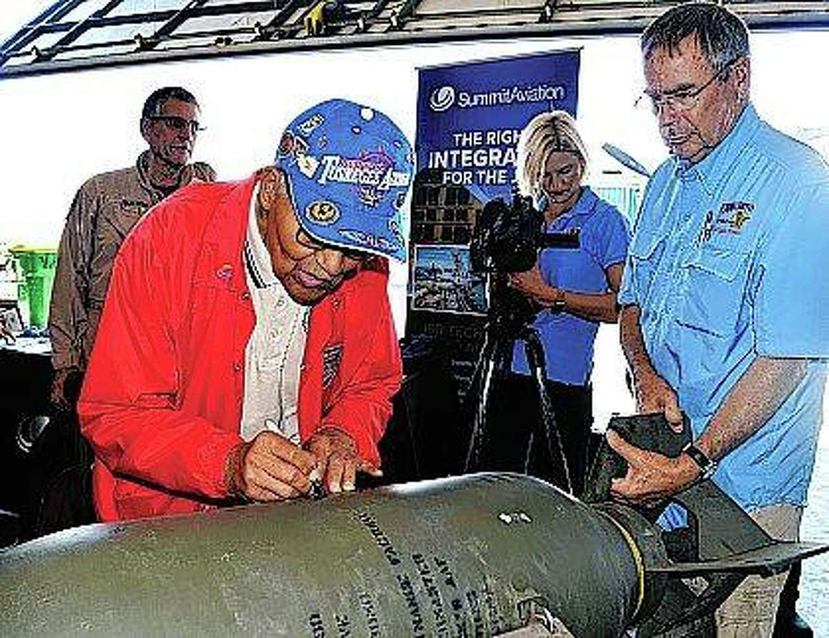 At the request of pilot/aviation historian Larry Kelley (right), retired Col. Charles McGee, a member of the Tuskegee Airmen, adds his name to previous signatures on a bomb casing during Wings & Wheels Pathways to Aviation Day.