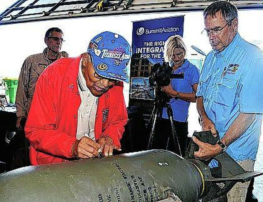 At the request of pilot/aviation historian Larry Kelley (right), retired Col. Charles McGee, a member of the Tuskegee Airmen, adds his name to previous signatures on a bomb casing during Wings & Wheels Pathways to Aviation Day. Photo: Glenn Rolfe | Delaware State News (AP)