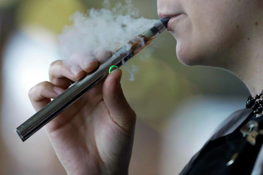 FILE - In this Friday, Oct. 4, 2019 file photo, a woman using an electronic cigarette exhales in Mayfield Heights, Ohio. Oregon regulators enacted a six-month ban Friday, Oct. 11, 2019, on the sale of flavored vape products in stores and online statewide amid an outbreak of illnesses that has sickened nearly 1,300 people nationwide and killed more than two dozen people, including two in Oregon. The Oregon Liquor Control Commission, which regulates the recreational marijuana market in the state, voted unanimously to approve the temporary sales ban. (AP Photo/Tony Dejak, File) Photo: Tony Dejak / Associated Press / Copyright 2019 The Associated Press. All rights reserved.
