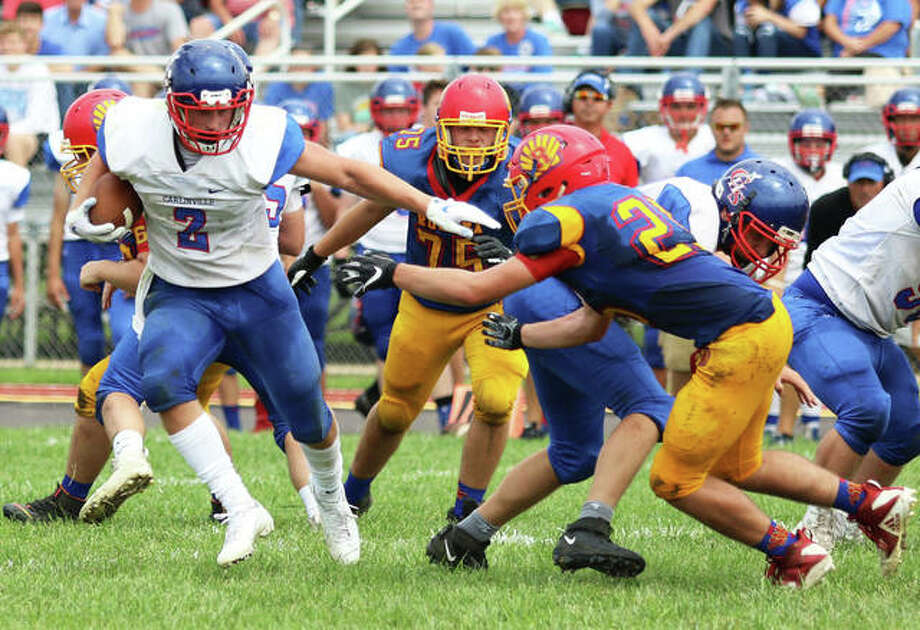 Carlinville's Colton DeLong (2) tries to elude Roxana linebacker David Pluester during a Week 1 SCC game in Roxana. DeLong on Friday night in Carlinville went over 1,000 rushing yards for the season with 252 yards and three TDs in a win over Hillsboro. Photo: Greg Shashack / The Telegraph