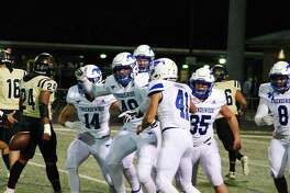 Friendswood's Matthew Reyes (49) is swarmed by teammates after blocking a punt against Richmond Foster Friday at Traylor Stadium.
