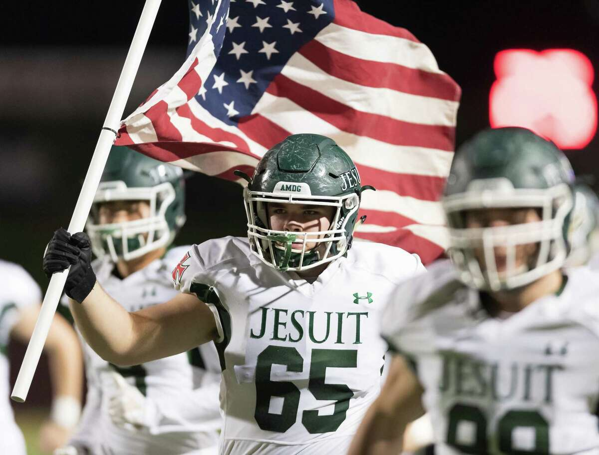 Barclay Briggs (65) of the Strake Jesuit Fighting Crusaders holds the American flag as he brings his team onto the field in a high school playoff game against the West Brook Bruins on Friday, November 23, 2018 at Abshire Stadium in Deer Park Texas.