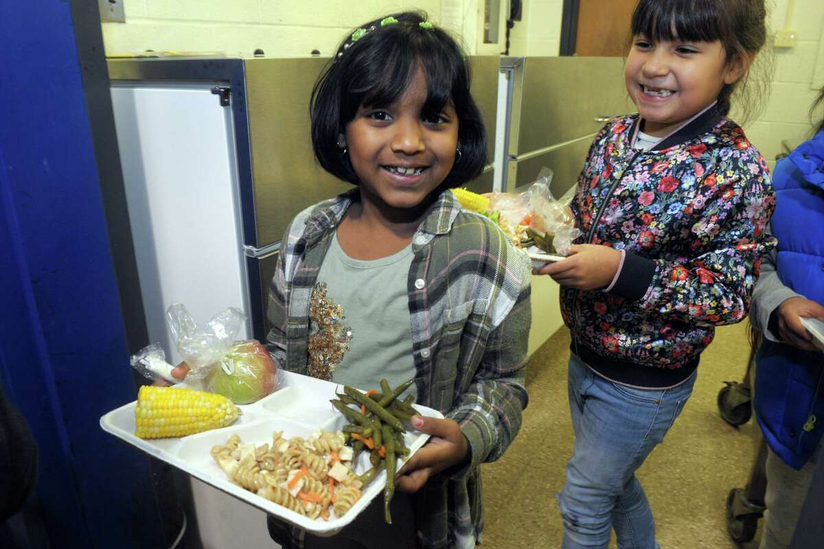 Second graders Isabella Sanchez, left, and Samaira Raman exit the food line with their lunches at Jefferson Elementary School, in Norwalk, Conn. Oct. 11, 2019. Norwalk schools have recently launched an initiative to serve healthier and locally sourced lunches to their students.
