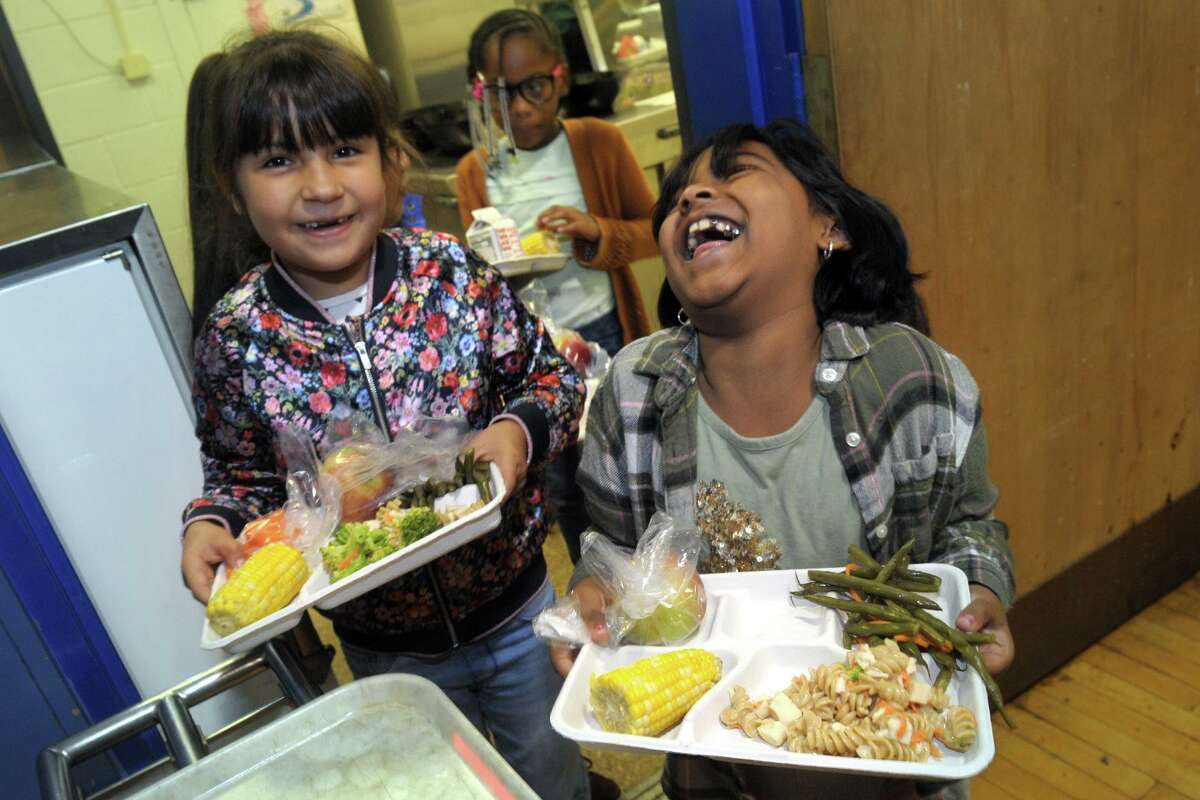 Second grader Samaira Raman, right, shares a laugh with classmate Isabella Sanchez as they exit the food line with their lunches at Jefferson Elementary School, in Norwalk, Conn. Oct. 11, 2019. Norwalk schools have recently launched an initiative to serve healthier and locally sourced lunches to their students.