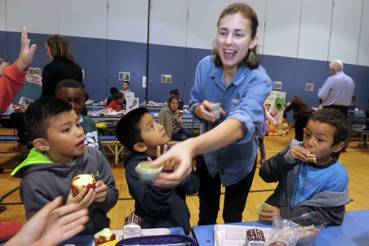 Meghan Hadley, a representative from FoodCorps, hands out samples of kale smoothies during lunch at Jefferson Elementary School, in Norwalk, Conn. Oct. 11, 2019. FoodCorps is working with Norwalk schools have recently launched an initiative to serve healthier and locally sourced lunches to their students.