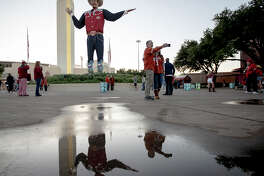 Texas fans take a selfie with Big Tex on the fairgrounds of the Texas State Fair before an NCAA college football game between Texas and Oklahoma at the Cotton Bowl on Saturday, Oct. 12, 2019, in Dallas. (Nick Wagner/Austin American-Statesman via AP)