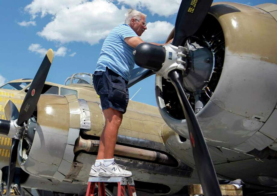 """In This July 1, 2019 photo, Ernest """"Mac"""" McCauley, a veteran pilot who volunteers with the Collings Foundation, works on one of the nine-cylinder radial engines on a B-17 Flying Fortress bomber on display at the Spokane International Airport in Spokane, Wash. McCauley, 75, of Long Beach, Calif., and his co-pilot were among seven people killed when the bomber crashed and burned Wednesday, Oct. 2, at Bradley International Airport in Windsor Locks, Conn. Photo: Jesse Tinsley / Associated Press / The Spokesman-Review"""