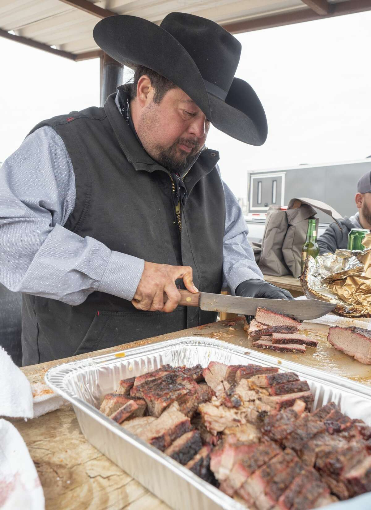 Joe Posas, with team This and That II and This is It II, cuts up brisket bites to hand out 10/12/19 as he and other teams cook brisket, chicken, chilli and other smoked treats outside the American Legion Post off Veterans Park Lane during the annual Patsy's Cook-off Breast Cancer Awareness competition. Tim Fischer/Reporter-Telegram