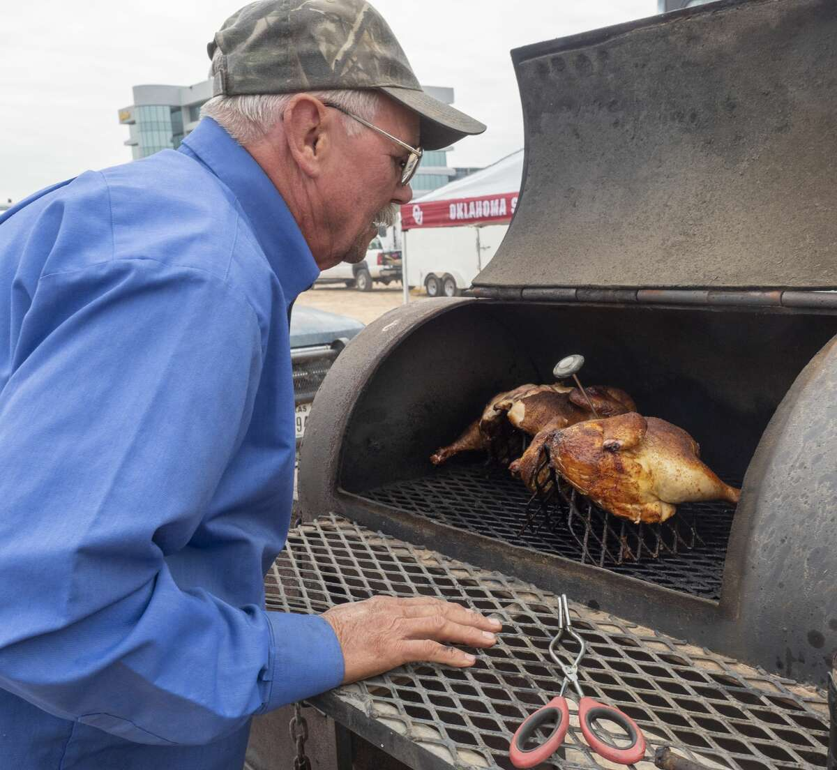 Buddy McGuire with team Black Sheep, checks the temperature of his whole chicken 10/12/19 as he and other teams cook brisket, chicken, chilli and other smoked treats outside the American Legion Post off Veterans Park Lane during the annual Patsy's Cook-off Breast Cancer Awareness competition. Tim Fischer/Reporter-Telegram