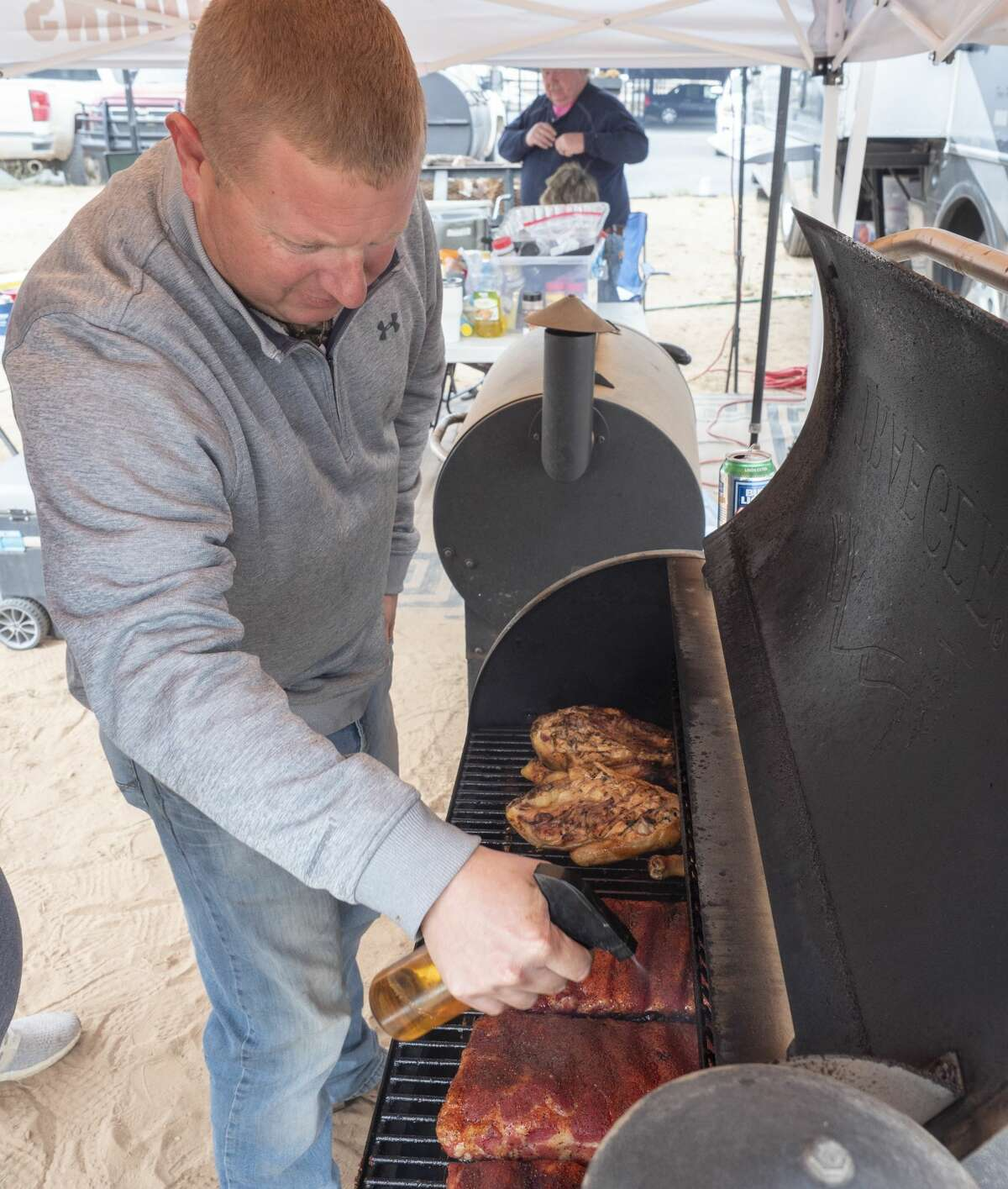 Brian Stephens with team Lazy Boy Cooking, sprays the ribs with a mixture 10/12/19 as he and other teams cook brisket, chicken, chilli and other smoked treats outside the American Legion Post off Veterans Park Lane during the annual Patsy's Cook-off Breast Cancer Awareness competition. Tim Fischer/Reporter-Telegram