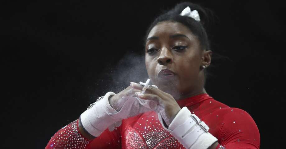 Simone Biles of the United States chalks her hands prior to her performance on the uneven bars in the women's apparatus finals at the Gymnastics World Championships in Stuttgart, Germany, Saturday, Oct. 12, 2019. (AP Photo/Matthias Schrader) Photo: Matthias Schrader/Associated Press