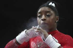 Simone Biles of the United States chalks her hands prior to her performance on the uneven bars in the women's apparatus finals at the Gymnastics World Championships in Stuttgart, Germany, Saturday, Oct. 12, 2019. (AP Photo/Matthias Schrader)