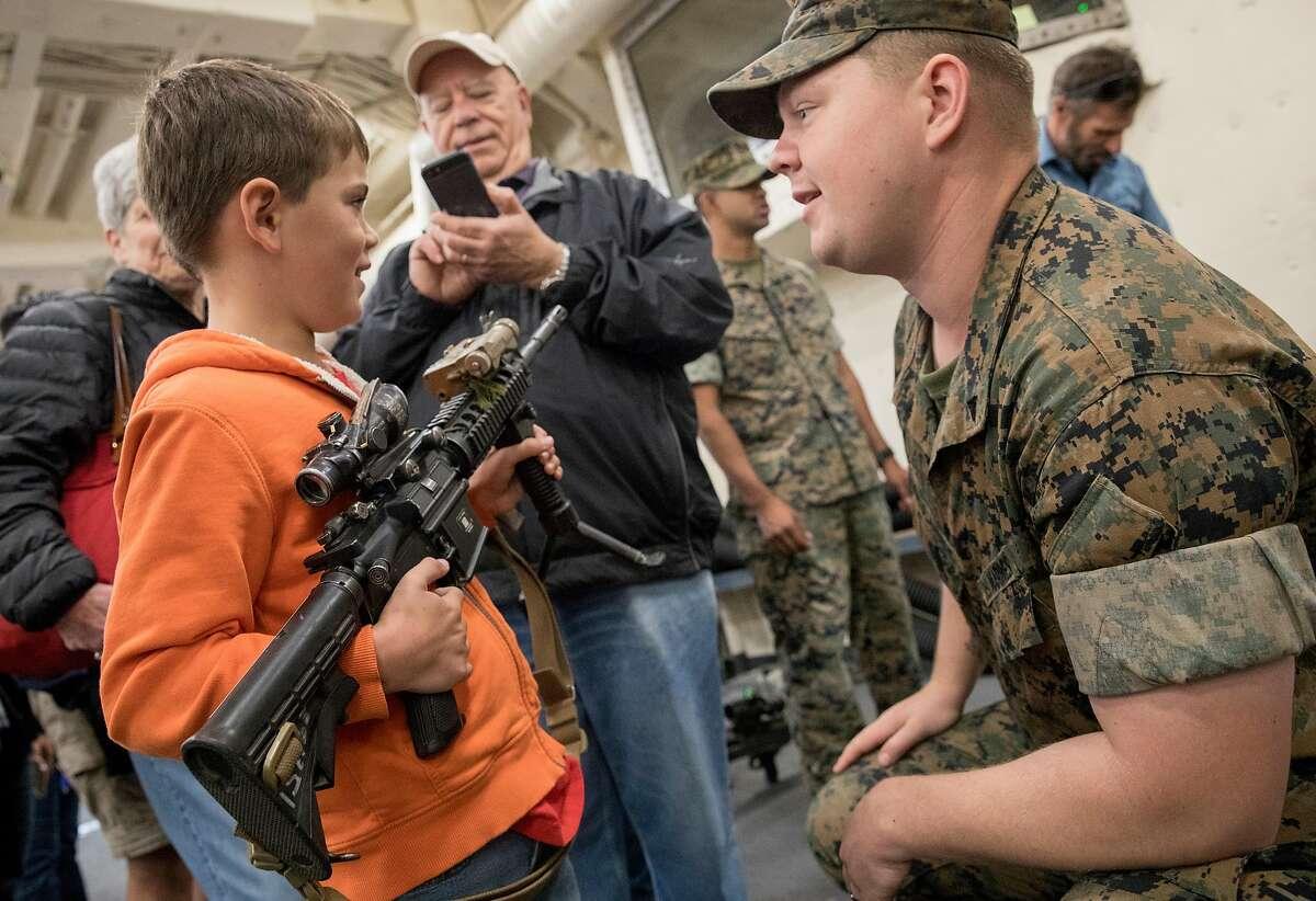 US Marine Matthew Hulslander (right) lets Luke D'Urso, 7, hold an M4 machine gun during a tour aboard the USS Somerset naval warship during Fleet Week festivities in San Francisco, Calif. Saturday, Oct. 12, 2019.