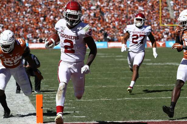 DALLAS, TEXAS - OCTOBER 12: CeeDee Lamb #2 of the Oklahoma Sooners runs for a touchdown against B.J. Foster #25 of the Texas Longhorns in the third quarter during the 2019 AT&T Red River Showdown at Cotton Bowl on October 12, 2019 in Dallas, Texas. (Photo by Ronald Martinez/Getty Images)