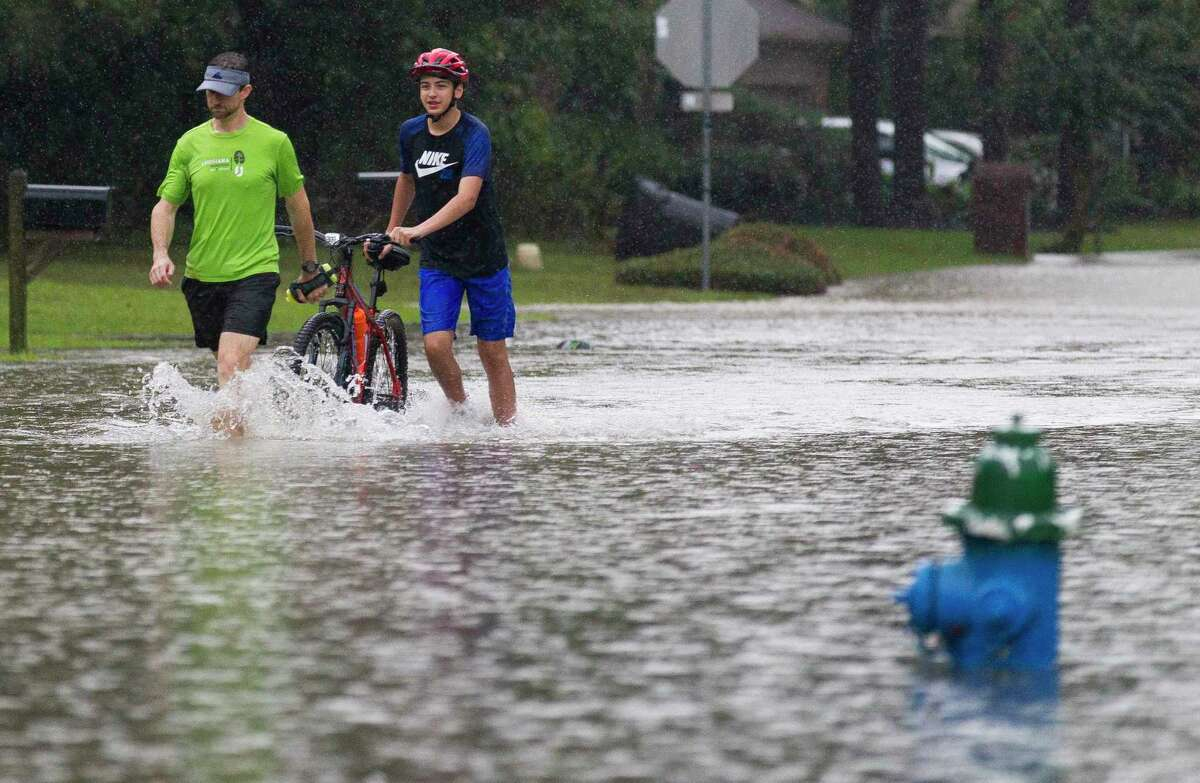 Charles and Andrew Thompson wade through a flooded street in the Elm Grove subdivision, Thursday, Sept. 19, 2019, in Kingwood.