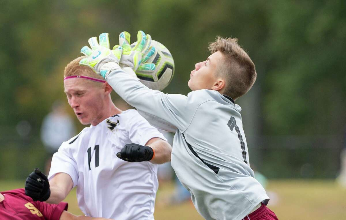 St. Joseph keeper Deaglan Prendergast takes the ball off Trumbull's Justin Horvath's head on Saturday. High school boys soccer action between St. Joseph high school and Trumbull High at St. Joseph, Saturday, Oct. 12.
