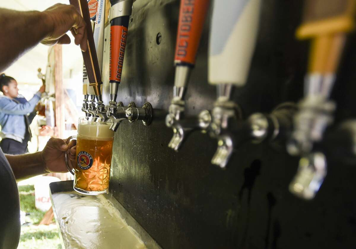 A bar attendant pours a beer out for people enjoying the beer, food and live music at Beaumont's Oktoberfest Saturday afternoon. Photo taken on Saturday, 10/12/19. Ryan Welch/The Enterprise