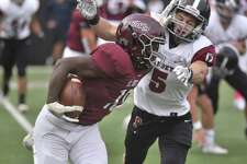 St. Luke's Shamond Moore (18) holds off Portsmouth Abbey's Victor Otero (5) during a football game at St. Luke's School in New Canaan on Saturday, Oct. 12, 2019.