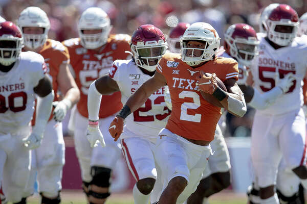 Texas running back Roschon Johnson (2) runs the ball against Oklahoma during an NCAA college football game at the Cotton Bowl, Saturday, Oct. 12, 2019, in Dallas. (Nick Wagner/Austin American-Statesman via AP)