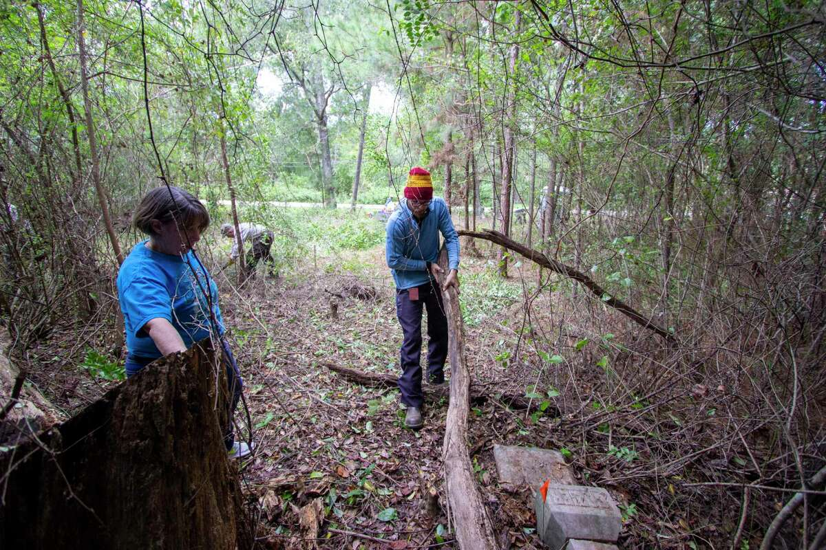 Volunteers Pam Ready and Mathew Whitmire pull a rotted branch away from the headstone of Jacob F. Cozier during a restoration project Saturday, October 12, 2019 at the Conroe Community Cemetery.