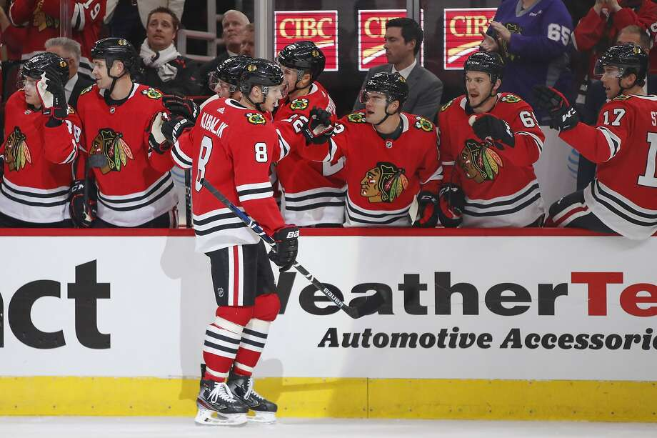 Blackhawks wing Dominik Kubalik (8) celebrates with teammates after scoring his first NHL goal in the first period against visiting San Jose on Thursday. Photo: Kamil Krzaczynski / Associated Press