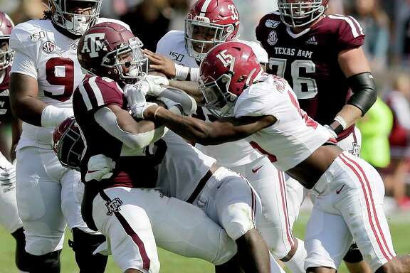 Texas A&M running back Isaiah Spiller (28) is wrapped up by the Alabama defense after a short gain during the first half of an NCAA college football game, Saturday, Oct. 12, 2019, in College Station, Texas.