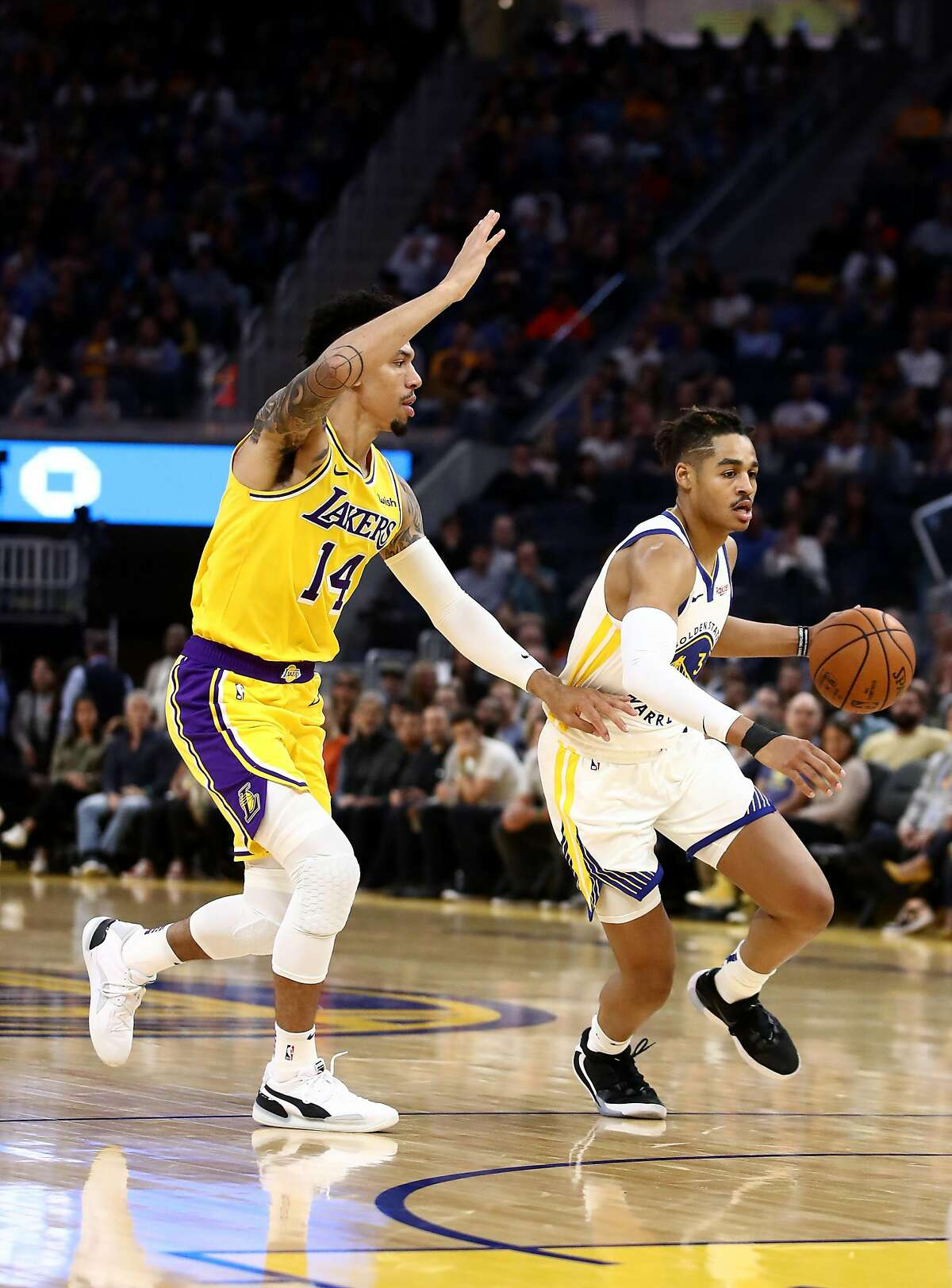 Jordan Poole (3) of the Golden State Warriors dribbles past Danny Green (14) of the Los Angeles Lakers at Chase Center on October 05, 2019 in San Francisco, California.