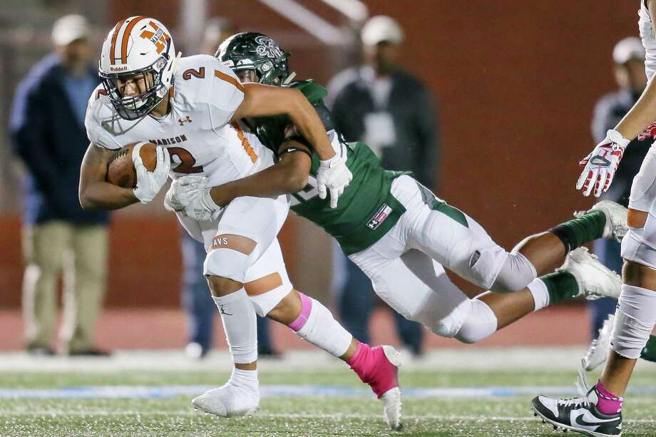 Madison's Darien Gill carries Reagan defender Richard Jones for some of his 225 yards rushing. Photo: Marvin Pfeiffer /Contributor / Express-News 2019