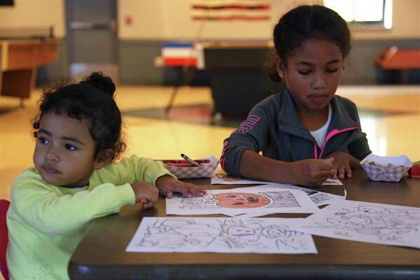 Dahlia Kuye, 2, of Trumbull, left, and her sister Violet, 6, do some artwork at the Easton Community Center's Family Octoberfest on Saturday, Oct. 12, 2019, in Easton, Conn.