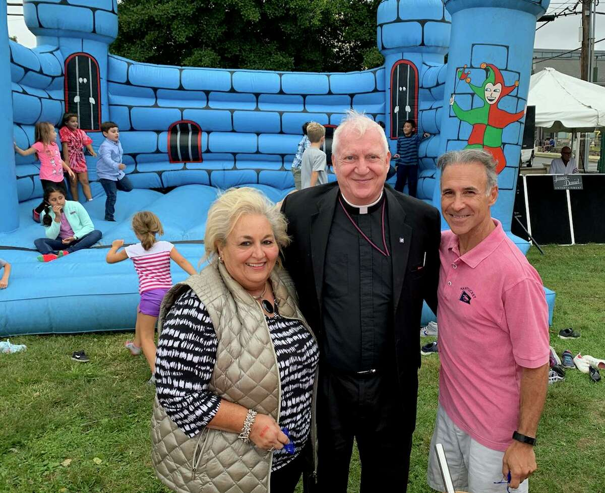 State Rep. Fred Camillo and Town Clerk Carm Budkins with the Rev. Carl D. McIntosh at the St. Roch Church picnic on Oct. 6. after they and other parishioners received awards for their volunteer work at the church.