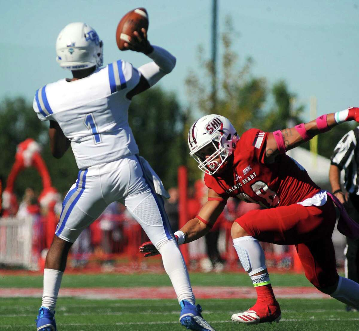Sacred Heart RJ Trimble-Edwards converges on Central Connecticut QB Aaron Winchester during football action in Fairfield on Oct. 5, 2019.
