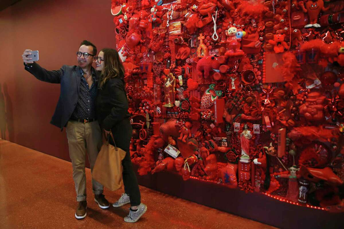 """Richard Garcia and his sister, Teresa Garcia, pose by """"Red Project,"""" an assemblage by Linda Pace, during the opening of Ruby City."""