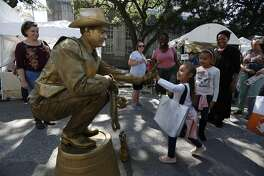 Davis Stumberg gives a high-five to Sage Purdue, 4, during the Bayou City Art Festival Sunday, Oct., 13, 2019 in Houston. The two-day festival showcases the works of over 300 of the finest artists in the world.