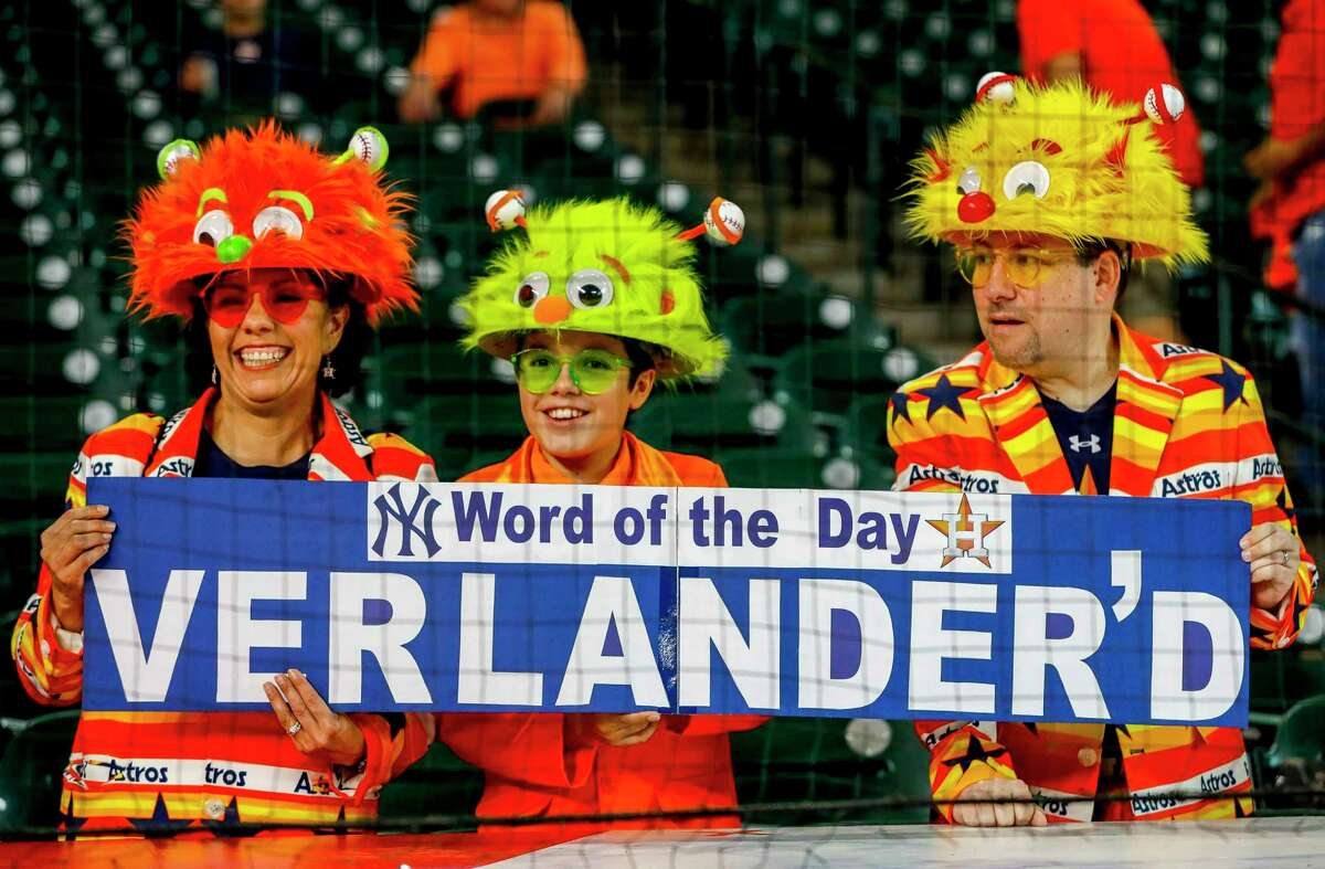 Monica Leon, Devin Opfer and Doug Opfer hold up a sign for Verlander during batting practice before Game 2 of the American League Championship Series at Minute Maid Park on Sunday, Oct. 13, 2019, in Houston.