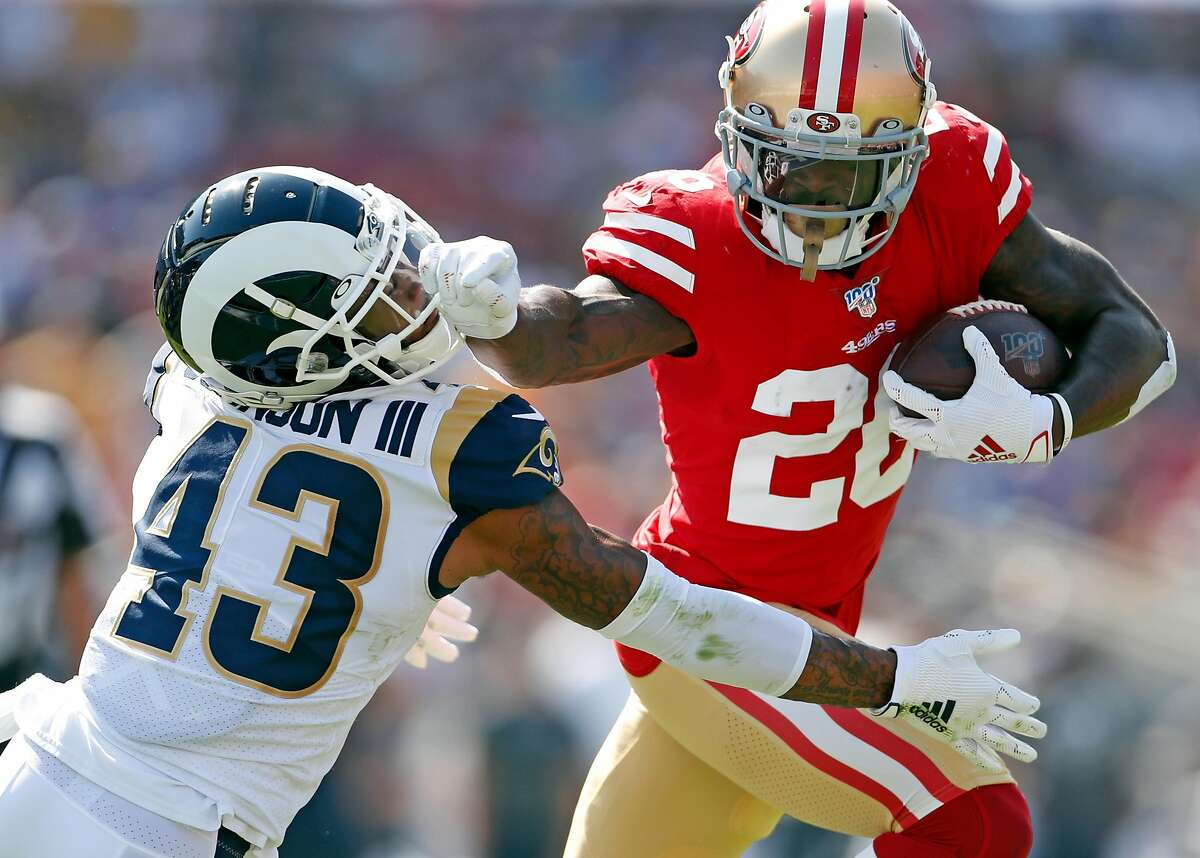 San Francisco 49ers' Tevin Coleman stiff arms Los Angeles Rams' John Johnson III during 2nd quarter touchdown run during NFL game at Los Angeles Coliseum in Los Angeles, Calif., on Sunday, October 13, 2019.