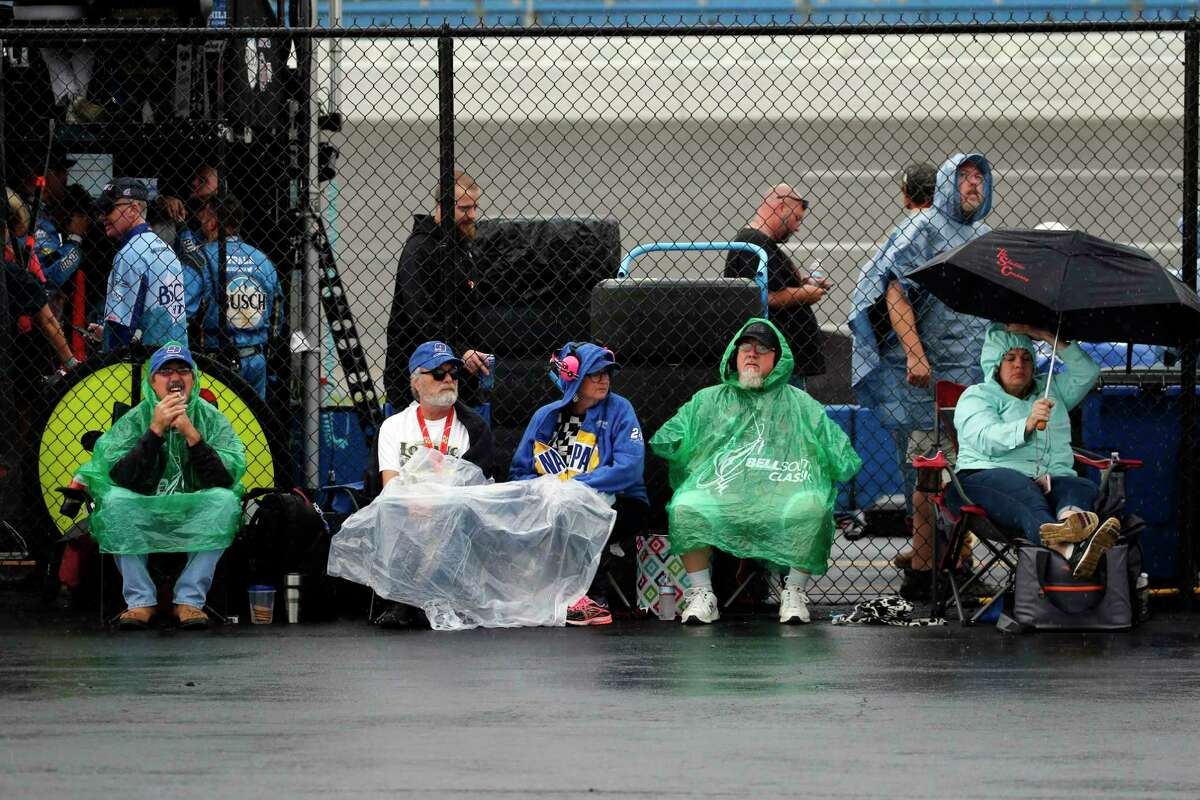 Fans sit in the rain as a NASCAR Cup Series auto race is delayed at Talladega Superspeedway in Talladega, Ala., Sunday, Oct. 13, 2019. (AP Photo/Butch Dill)