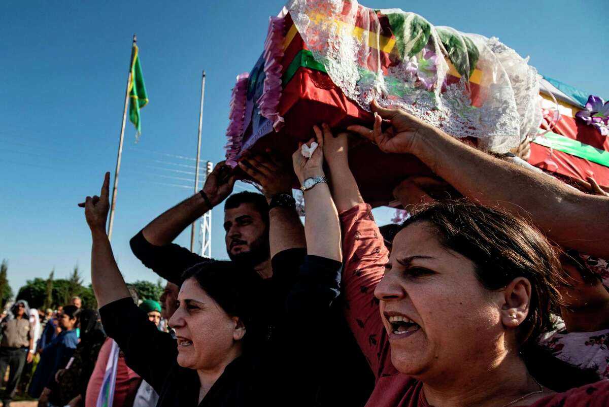 """Mourners carry the coffin of Kurdish political leader Hevrin Khalaf during a funeral, for her and others including civilians and Kurdish fighters, in the northeastern Syrian Kurdish town of Derik, known as al-Malikiyah in Arabic, on October 13, 2019. - Pro-Ankara fighters taking part in a Turkish offensive on Kurdish-held border towns in northeastern Syria """"executed"""" at least nine civilians including a female politician on Saturday, the Syrian Observatory for Human Rights said. (Photo by Delil SOULEIMAN / AFP) (Photo by DELIL SOULEIMAN/AFP via Getty Images)"""
