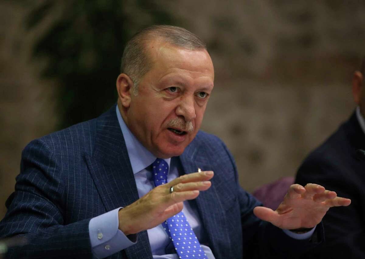 Turkey's President Recep Tayyip Erdogan speaks to Turkish journalists, in Istanbul, Sunday, Oct. 13, 2019. Erdogan has rejected offers for mediation with Syrian Kurdish fighters as the Turkish military continues its offensive against them in northern Syria. (Presidential Press Service via AP, Pool)