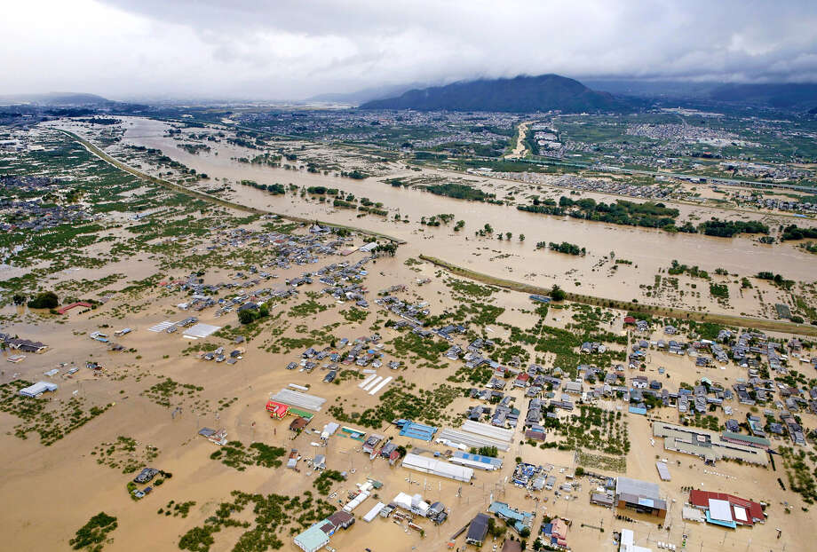An aerial photo shows a flooded residential area of Nagano, Japan, on Sunday after a dike of the Chikuma River was breached. Photo: Japan News-Yomiuri / Japan News-Yomiuri