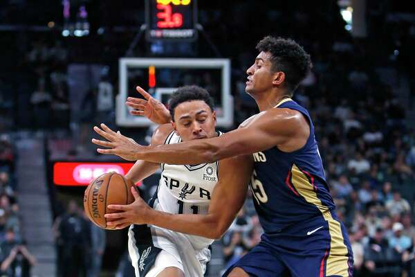 Bryn Forbes #11 of the San Antonio Spurs drives on Frank Jackson #15 of the New Orleans Pelicans on Sunday, October 13, 2019.