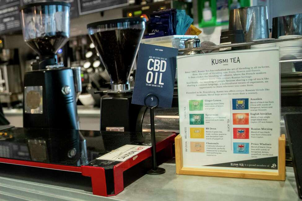In this Tuesday, Oct. 8, 2019, photo a sign advertising shots of CBD oil available as an addition to beverages is seen on a countertop at at Le District in the Financial district of New York. Food and drink spiked with the cannabis derivative CBD is still being sold in New York City, months after health officials banned it from edibles because of safety concerns. City health officials announced the CBD ban in February, but it took establishment owners by surprise, so they were offered a grace period until Oct. 1. (AP Photo/Mary Altaffer)