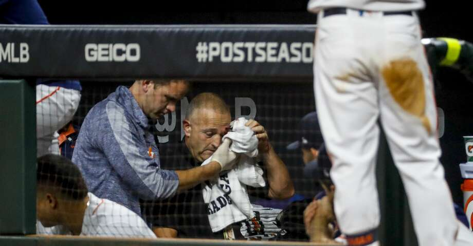 An injured staff member is escorted out of the Astros dugout after being struck by a foul ball hit by Houston Astros left fielder Michael Brantley (23) during the fifth inning of Game 2 of the American League Championship Series at Minute Maid Park on Sunday, Oct. 13, 2019, in Houston. Photo: Brett Coomer/Staff Photographer