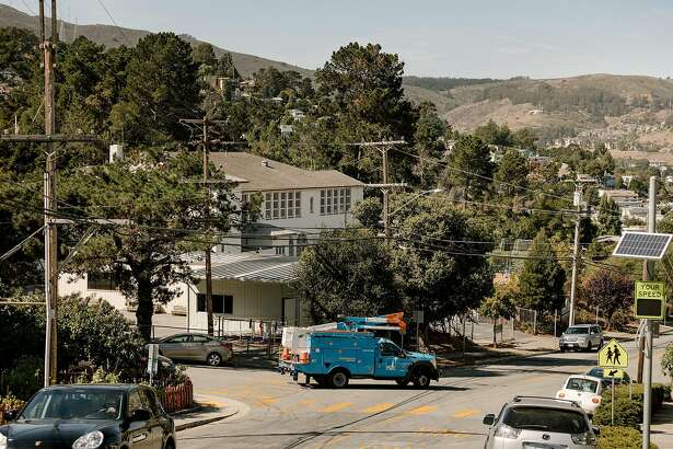 A Pacific Gas & Electric truck drives through a neighborhood as the company turned off power to broad areas, including urban and suburban development far from the risk of fire, in Brisbane, Calif., Oct. 10, 2019. PG&E, California's largest utility, used rolling blackouts this past week to protect dry forests from live power lines that could spark or overheat and set wildfires. (Jason Henry/The New York Times)