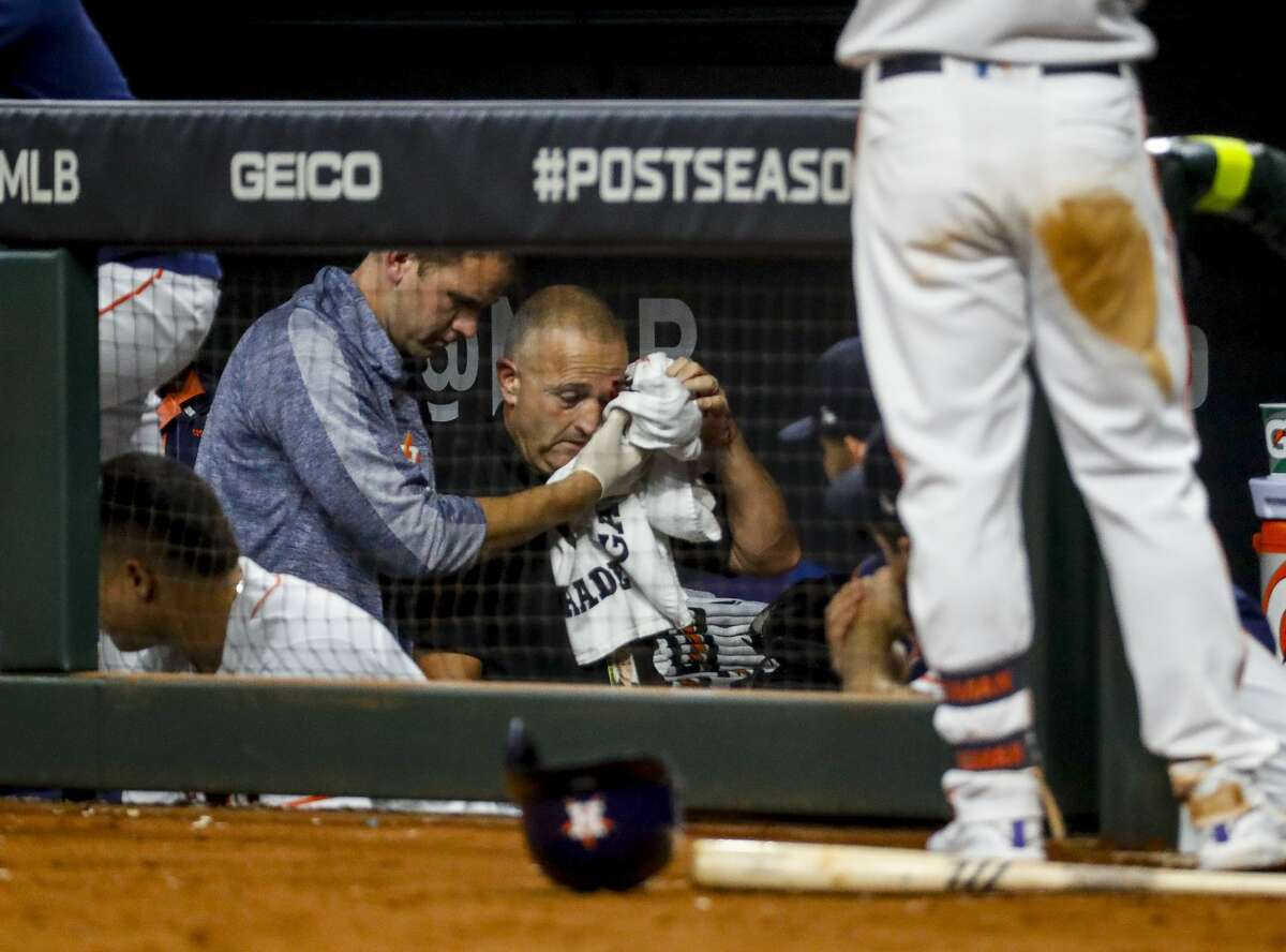 An injured staff member is escorted out of the Astros dugout after being struck by a foul ball hit by Houston Astros left fielder Michael Brantley (23) during the fifth inning of Game 2 of the American League Championship Series at Minute Maid Park on Sunday, Oct. 13, 2019, in Houston.
