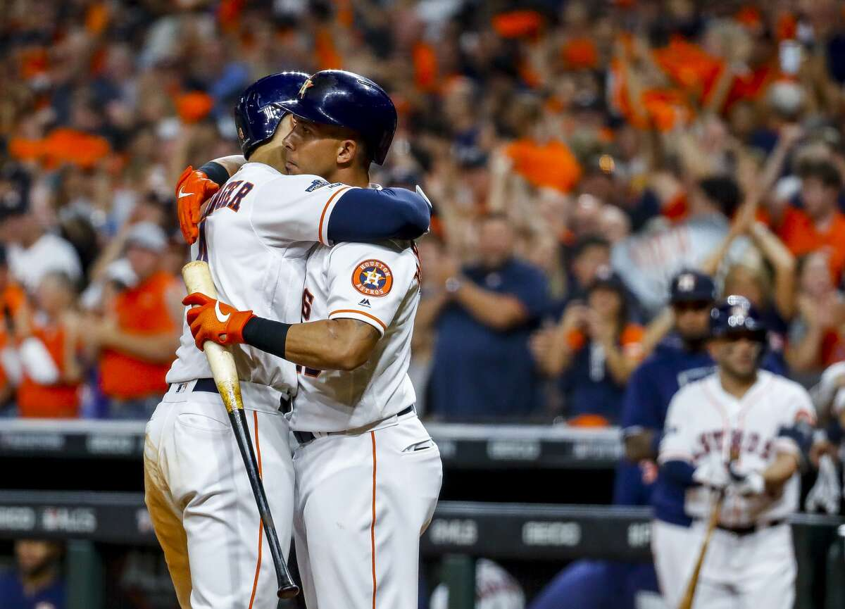 Houston Astros center fielder George Springer (4) is hugged by left fielder Michael Brantley (23) after Springer hit a solo home run to tie the game 2-2 during the fifth inning of Game 2 of the American League Championship Series at Minute Maid Park on Sunday, Oct. 13, 2019, in Houston.